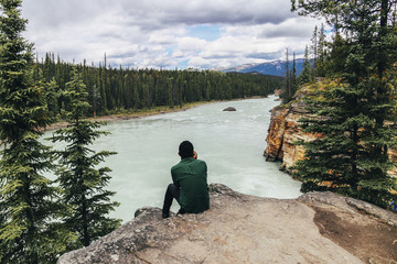 Man looking at view while sitting on cliff at Jasper National Park Fotobehang