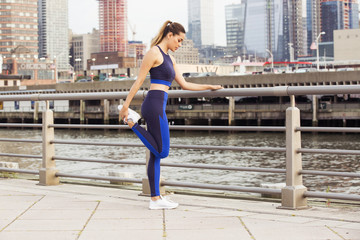 Side view of woman stretching leg while standing on bridge in city