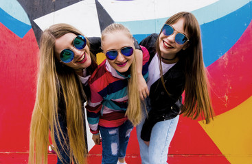 Portrait of happy female friends wearing sunglasses standing against graffiti wall