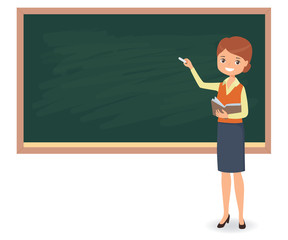 Young female teacher is writing chalk on a school blackboard