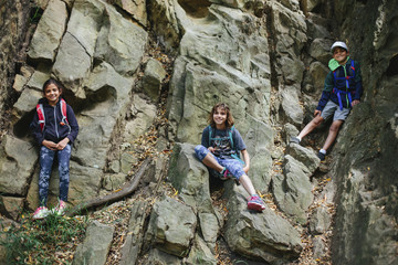 Low angle portrait of happy siblings climbing on rocks