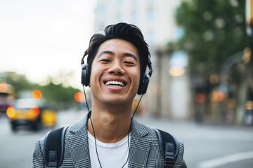 Portrait of happy businessman listening music in city