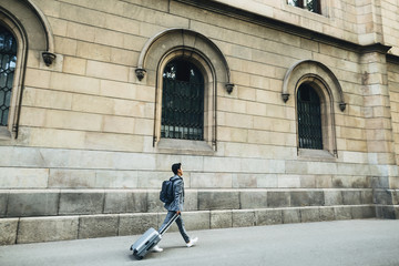 Side view of businessman with luggage walking on footpath against building