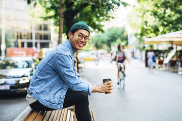 Portrait of man holding disposable cup while sitting on bench