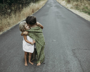 Brother kissing sister while standing on country road