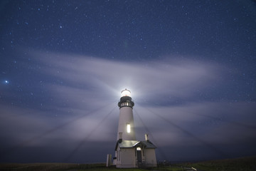 Low angle scenic view of Yaquina Head Lighthouse on shore against star field