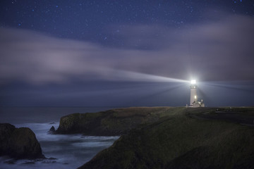 Scenic view of Yaquina Head Lighthouse on shore against star field