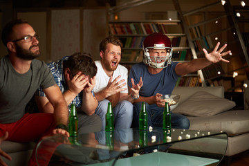 Four friends watching game of american footbal, showing frustration