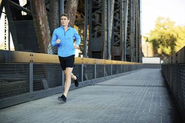 Full length of man running while exercising on bridge in city