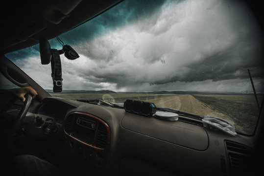 Cropped image of man driving car against stormy clouds