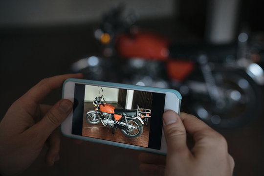 Cropped hands of woman photographing motorcycle at workshop