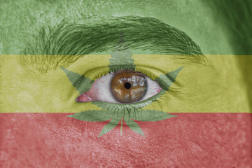 Human face and eye painted with flag of Rasta