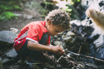 Side view of boy exploring on rock