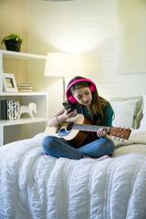 Teenage girl listening music through smart phone while sitting with guitar in bedroom