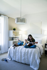 Girl using smart phone while sister playing guitar on bed in bedroom