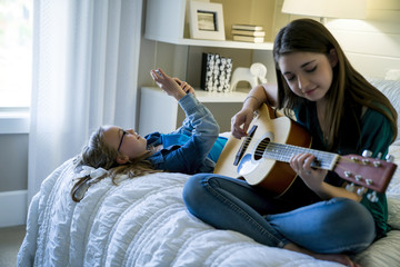 Girl using smart phone while sister playing guitar on bed