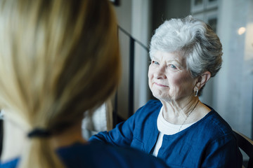 Happy senior woman looking at home caregiver