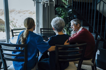 Senior couple and home caregiver sitting at dining table