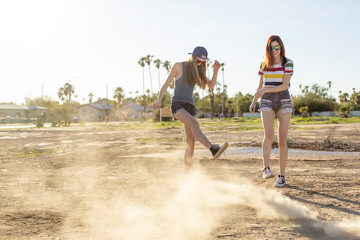 Happy female friends playing in dust on land against clear sky
