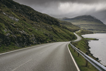 Winding road against stormy clouds