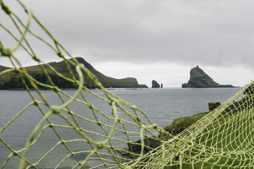 Rock formations in sea against cloudy sky with fishing net in foreground