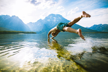 Man diving into lake against mountains and sky