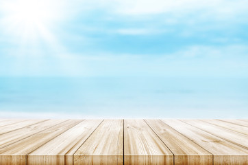 Empty wooden table top with blurred sea and sky background. Abstract background.