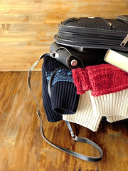 Suitcase full of clothes, book, camera and wallet for a trip. Travel concept