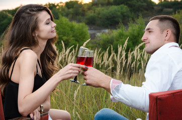 boy and girl outdoors drinking wine.