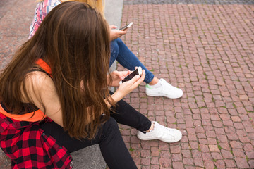 Happy teenage girls having fun spend time together in the city park