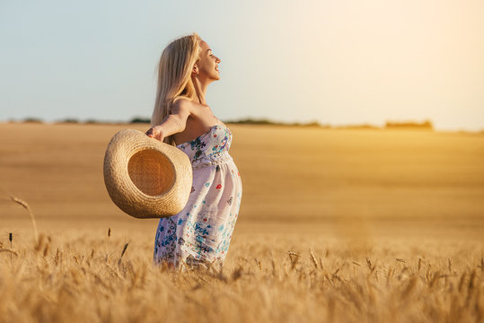 A young pregnant woman in a wheat field Concept photo of pregnancy, pregnant woman, newborn and baby.