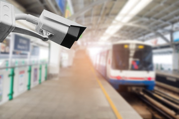 cctv security camera with abstract blur of sky train station.