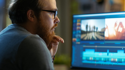 Male Video Editor Works with Footage and Sound on His Personal Computer. He Works in a Cool Office Loft. Wall mural