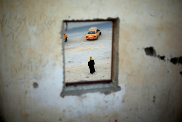 A Palestinian woman is seen through a window as she waits for the return of her relatives after performing the annual Haj pilgrimage in Mecca, at Rafah border crossing in the southern Gaza Strip