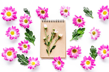 Floral pattern with pink flowers, green leaves and notebook on white background top view