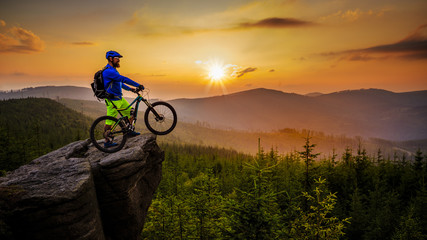 Mountain biker cycling in autumn mountains forest landscape. Man cycling MTB flow trail track. Outdoor sport activity.