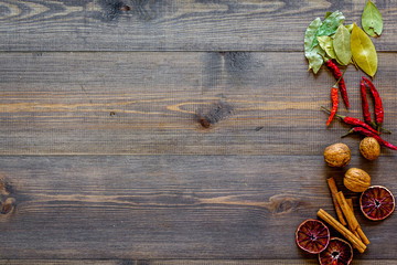 Kitchen table with spices and dry herbs on wooden kitchen background top view mock up