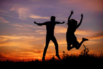 A young man with his girlfriend jump on background sunset silhouette