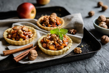 Fruit tartlets filled with caramelized apple pieces, cinnamon and walnuts