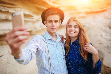 Attractive man with a beautiful woman are hugging and smiling. They are making selfie on the background of sand quarry