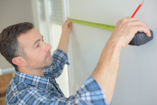 man with pencil measuring wall
