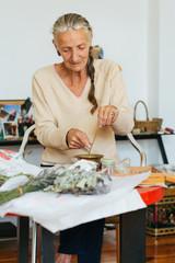 Indoor Portrait of Elderly Female Herbalist Making Natural Incense Stick