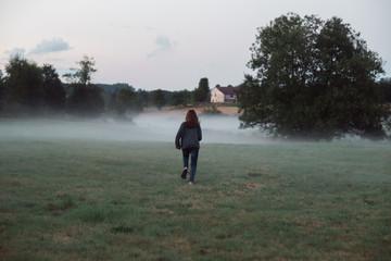 teen running in misty field