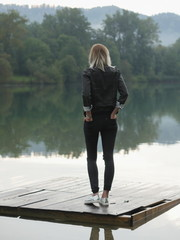 Back view of blonde woman in casual clothes on wooden pallet ove