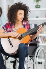 girl handicapped guitarist sitting on wheelchair