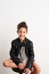 Smiling teen girl in leahter jacket sitting on a stool