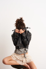 Studio portrait of offended girl hiding face with leather jacket