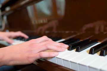 Closeup of hands on piano keyboard