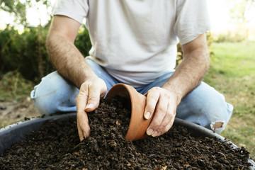 Gardener filling a terra cota pot with compost