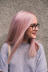 Smiling young girl with pink hair in eyeglasses